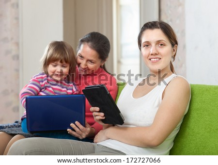 Two women and child with electronic devices on sofa in living room