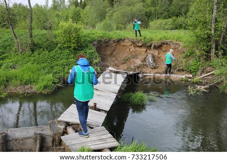 Two women and girl go on wooden bridge over small river in green forest
