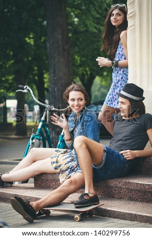 Two women and man communicate with each other. Outdoors - stock photo