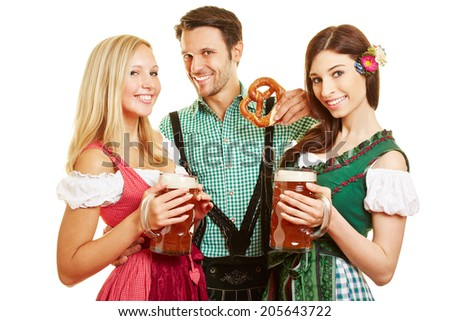 Two women and man with beer and pretzel at Oktoberfest in Bavaria - stock photo