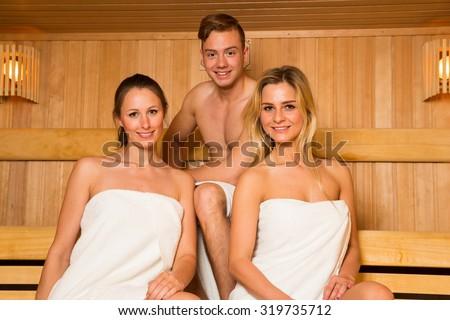 Two women and one man posing in wellness sauna - stock photo