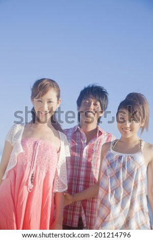 Two women and the man smiling under the blue sky