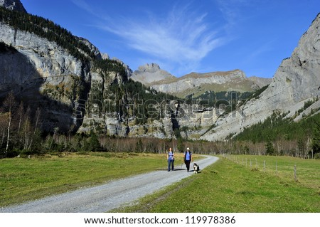 Two women and their dog walking in the alpine valley of Gasteretal, above Kandersteg, in Switzerland. Space for text in the sky.