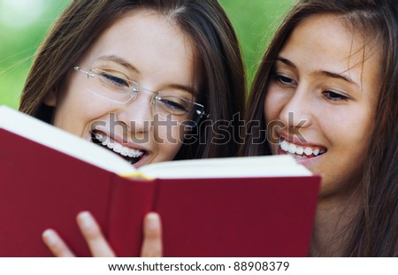 Two women are cheerful beautiful young in the summer the park are holding red book, read - stock photo