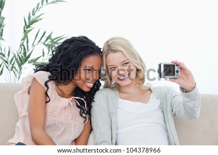 Two women are sitting down on a couch taking a photo of themselves with a camera - stock photo