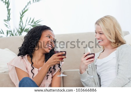 Two women are talking and drinking wine while sitting on the floor