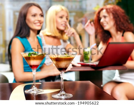 Two women at laptop drinking cocktail in a cafe.Sharpness on  glass - stock photo