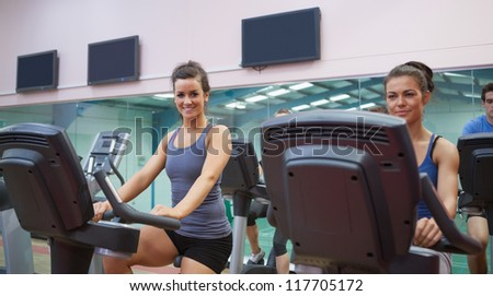 Two women at spinning class in gym - stock photo