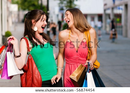 Two women being friends shopping downtown with colorful shopping bags, they are walking down a street having fun - stock photo