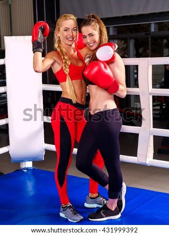 Two women boxer wearing red gloves posing in boxer ring. - stock photo