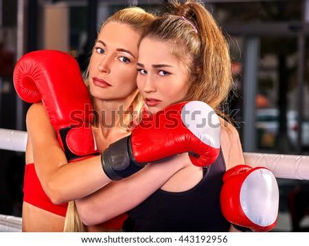 Two women boxer wearing red gloves posing in ring. - stock photo