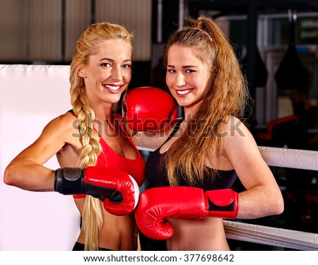 Two  women boxer wearing red  gloves posing in ring. Martial arts. - stock photo