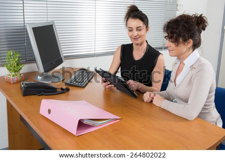 Two women chat to each other in the office with one woman having her laptop - stock photo