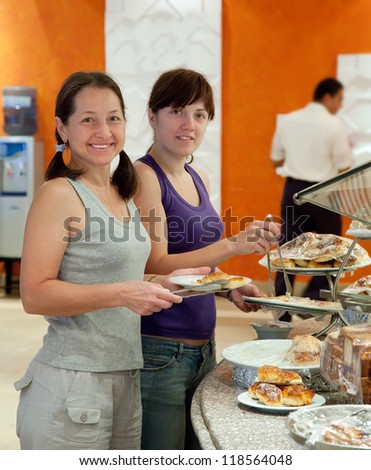 Two women  chooses sweet pastry in buffet at hotel