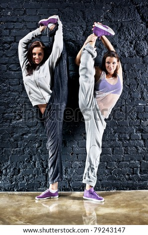 Two women dancers. On wall background. - stock photo