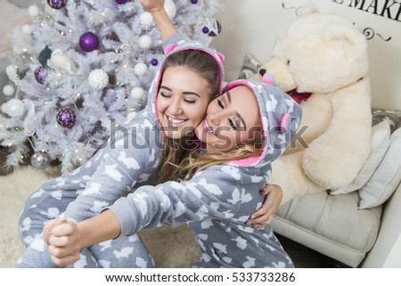 two women dancing in pajamas and laughing