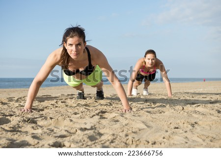 Two women doing pushups on a beach during an intense workout - stock photo