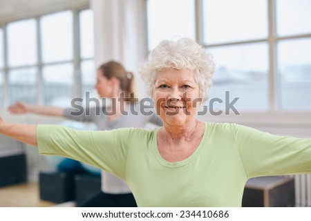 Two women doing stretching and aerobics workout at gym. Senior woman with her trainer in background during physical training session - stock photo