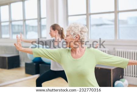 Two women doing stretching and yoga workout at gym. Female trainer in background with senior woman in front during physical training session - stock photo
