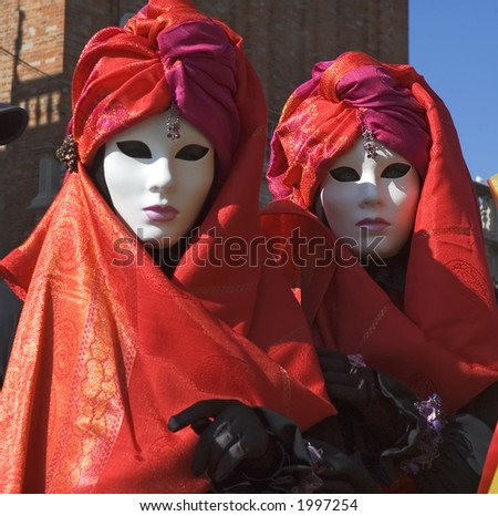 Two women dressed for Carnivale,the Mardi Gras of Europe, in Saint Marks Square,Venice,Italy. - stock photo