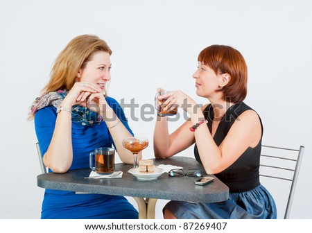 Two women drinking tea at the table - stock photo