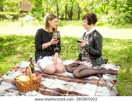 Two women drinking wine and talking at picnic in park - stock photo