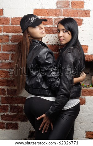 Two women embrace red bricks wall background. More images of this models you can find in my portfolio - stock photo