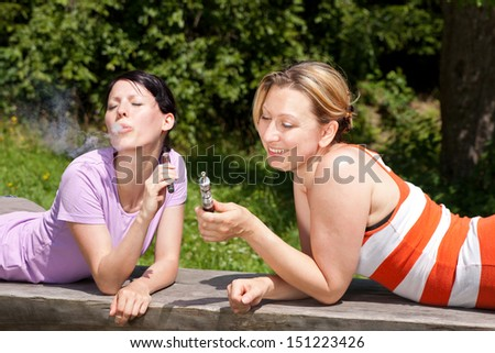 two women enjoy e-cigarette in nature - stock photo