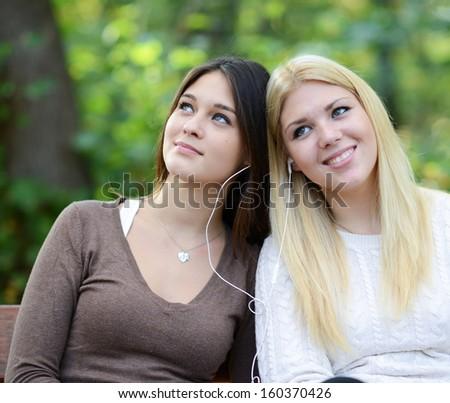 Two women enjoying nature whil listening to music - stock photo