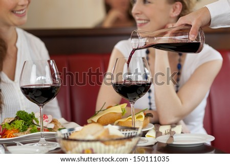Two women enjoying red wine sitting eating a meal in a restaurant and chatting while the waiter replenishes their glasses