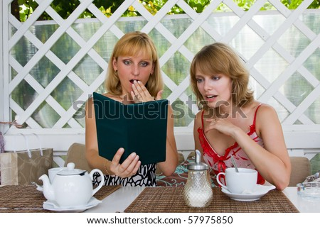 Two women expressed shock at the big bill. Friends having coffee in cafe. Female friends talking and drinking in coffee shop. - stock photo