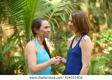 Two women expressing a truce or a greeting by shaking hands - stock photo
