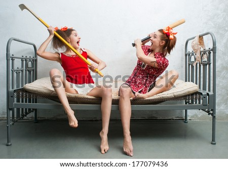 Two women fight on the bed - stock photo