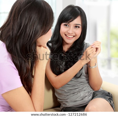 Two women friends chatting on the couch at home - stock photo