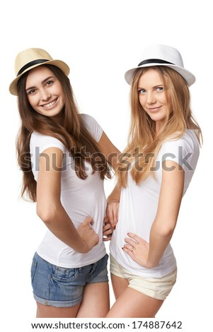 Two women friends having fun. Two happy girls in straw hats and white tshirts posing against white background - stock photo