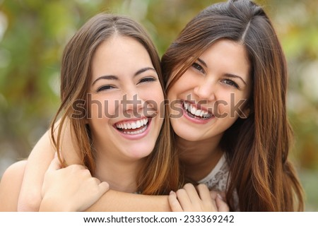 Two women friends laughing with a perfect white teeth with a green background - stock photo