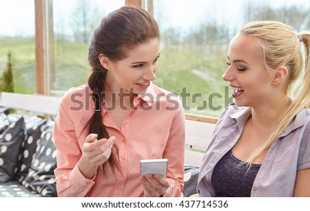 two women friends talking holding coffee cups in a house terrace - stock photo