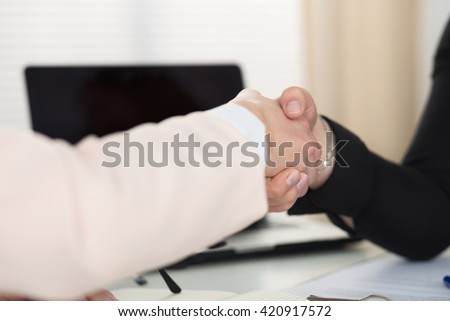 Two women handshake in office closeup. Businesswomen shaking hands. Serious business, partnership and collaboration concept. Partners made deal and sealed it with handclasp. Formal greeting gesture - stock photo