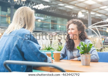 Two women having a coffee together and enjoying life in London. They are on their mid twenties, one blonde and one brunette, looking each other and sitting at the table in a cafe.
