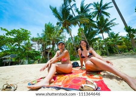 Two women having fun on a tropical beach - stock photo
