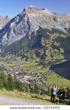 Two women hikers and their dog, beside a bench, looking out over the Swiss town of Kandersteg - stock photo