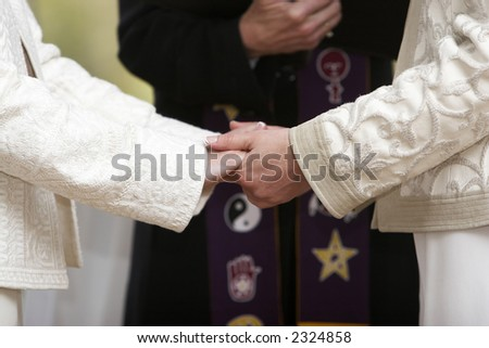 Two women holding hands during a wedding celebration - stock photo