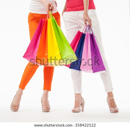 Two women holding  multicolored shopping bags, white background - stock photo