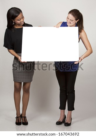 two women holding white board on light grey background - stock photo