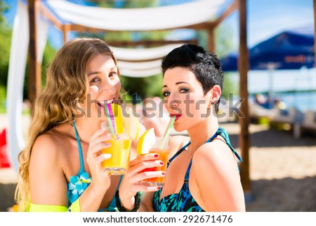 Two women in beach bar drinking cocktails