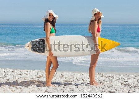 Two women in bikinis holding a surfboard on the beach
