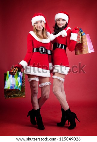 Two women in dressed as Santa, with shopping bags . on red background .