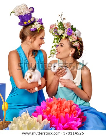 Two women in easter style holding white nice rabbits and flowers. Isolated.