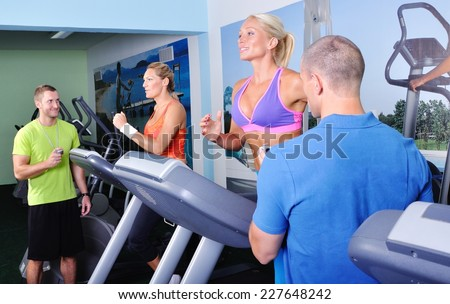 Two women in gym exercising with personal fitness trainer - stock photo
