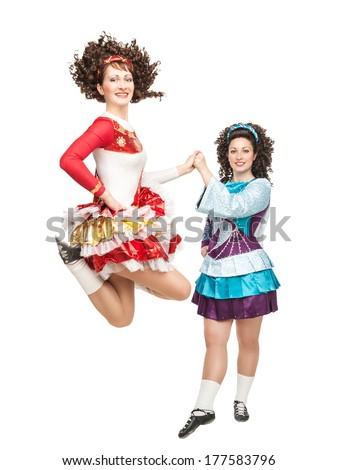 Two women in irish dance dress dancing - stock photo